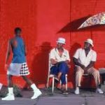 A screenshot from Spike Lee's Do the Right Thing. Four young Black men walk near three seated older Black men.